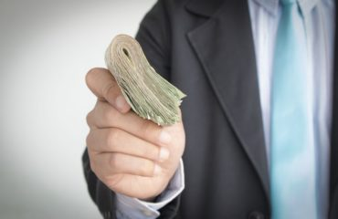 businessman with a lot of money in hand finance concept.